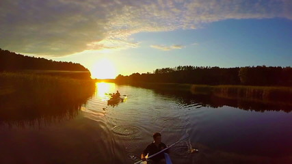 Sunset over river, silhouettes of people in boats, traveling