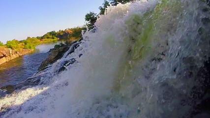 Closeup, waterfall falling into river, beautiful nature, sunset