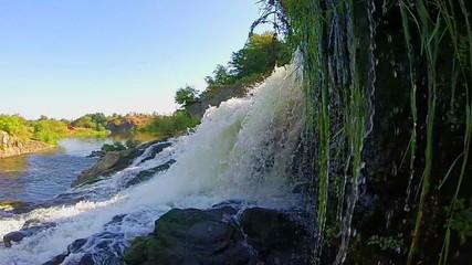 Turbulent waterfall splashing against rocks, river, wild nature