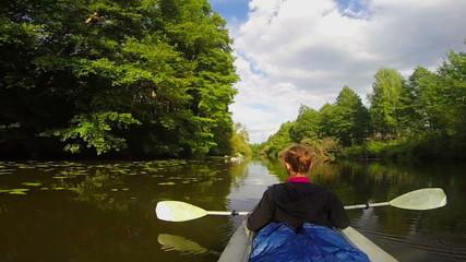 Girl traveler sitting in kayak, resting. Wide river, slow motion