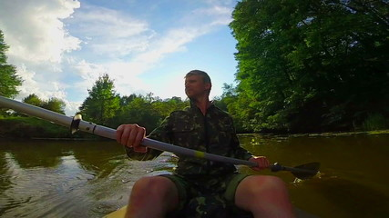 Young man paddling canoe on river. Action camera, slowmotion