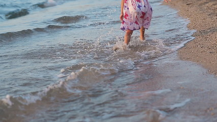 Little girl runing along the beach in sundress in slow motion
