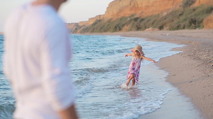 Little girl running along the beach to her father in slow motion