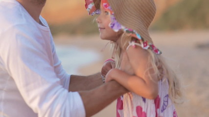 Father picks up little girl in hat on sea in slow motion