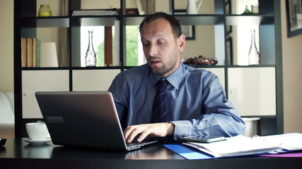 Young businessman talking bad news to camera sitting by desk