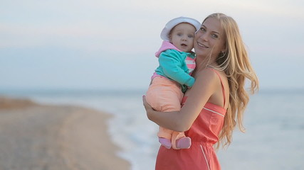 Young mother with long blond hair holding baby in her arms while