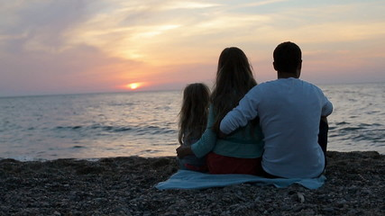 Happy family sitting in the sunset near the sea in slow motion