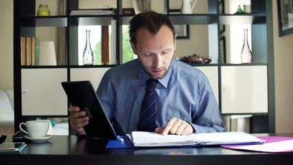 Young businessman chatting on tablet and reading documents