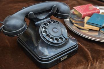 old vintage rotary dial black telephone on brown velvet