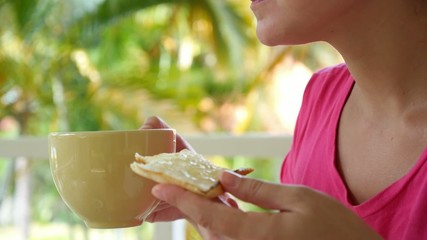 Female Eating Toast and Drinking Coffee or Tea
