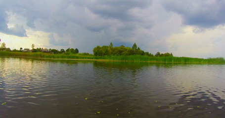 Wide river, countryside. Nature before storm, rapid motion