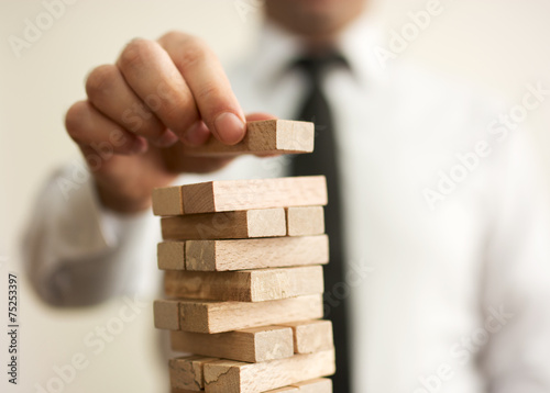 Businessman putting last block to the tower - 75253397