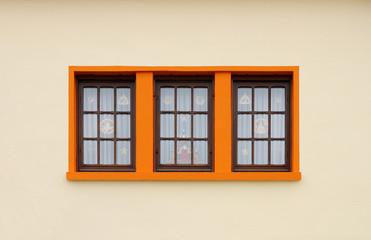 Dunkle Holzfenster mit orangeroter Fenstereinfassung