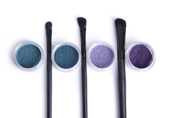 Top view of mineral eye shadows in pastel colors and brushes