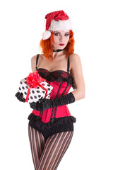 Redhead pinup girl in red corset and Santa Claus hat, holding gi