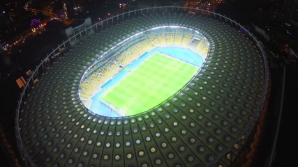 Illuminated football stadium, field and seating, view from above