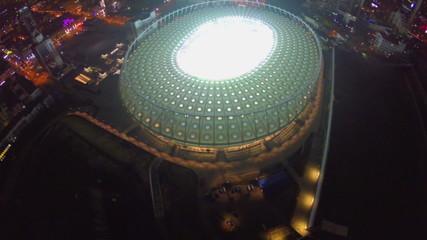 Flying high above the illuminated stadium, night city lights