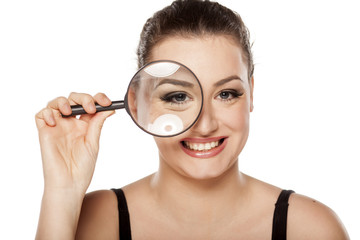 smiling young woman looking through a magnifying glass