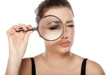 suspicious young woman looking through a magnifying glass