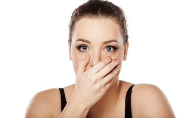 surprised young woman covering her mouth with her hand