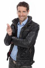 Lässiger Mann in Lederjacke zeigt nach vorne