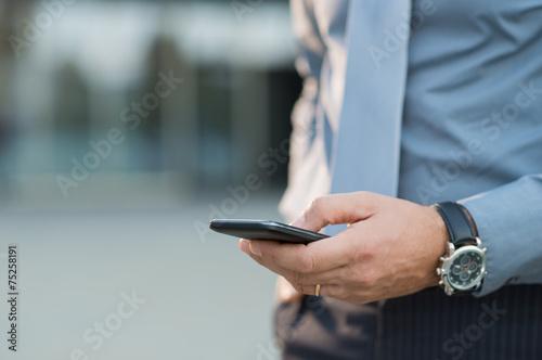 Leinwanddruck Bild Businessman Holding Smartphone