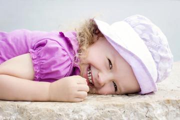 Happy little girl lying on the rock