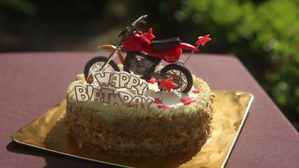 close up Birthday cake with nuts vanilla cream motorcycle figure