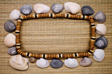 frame with beads and shells on straw background