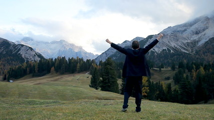 Business man feeling the freedom of the mountains