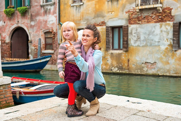Baby girl and mother poiting on copy space while in venice