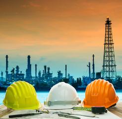 safety helmet on engineer working table against beautiful oil re