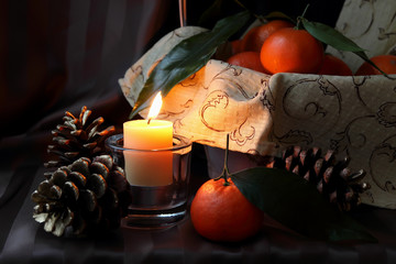 Burning candle and tangerines.