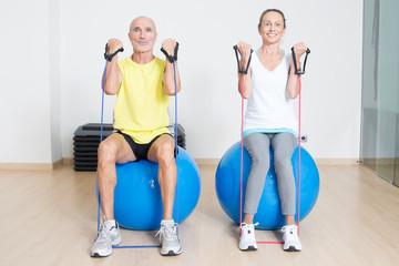 Zwei Senioren beim Seiltraining auf Fitnessball
