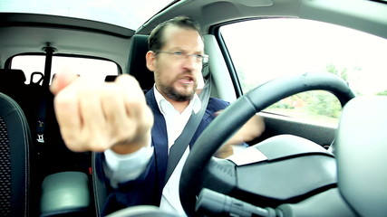 Happy successful business man in car driving celebrating