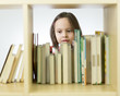 Young girl looking at books on bookshelf