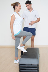 Coach hilft aelterer Frau beim step training