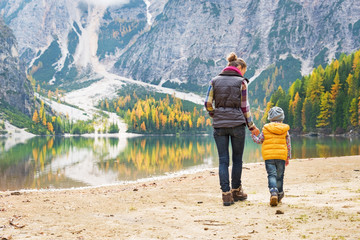 Mother and baby walking on lake braies in south tyrol, italy