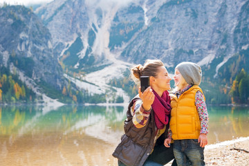 Happy mother and baby making selfie on lake braies in italy