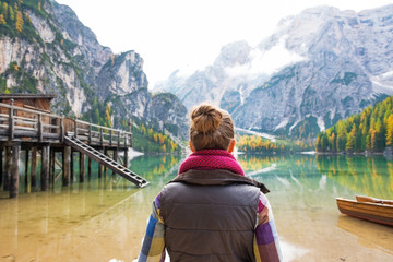 Young woman on lake braies in south tyrol, italy. rear view