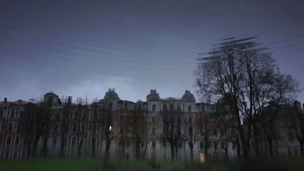Houses and trees in the city are reflected in the waves