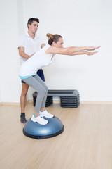 Trainer hilft Rentnerin mit Fitnessübung