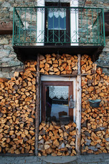 woodpile and window of a typical chalet in italian alps