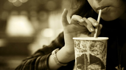 Old film effect: young girl drinks cold beverage with a straw