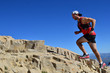 Man running on a high mountain trail - 75281352