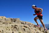 Man running on a high mountain trail