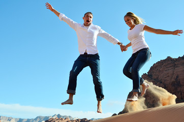 Couple Flying through the air above sand dune
