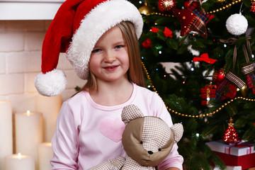 Little girl in Santa hat  with teddy bear near fir tree