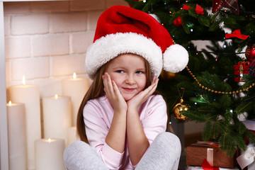 Little girl in Santa hat sitting near fir tree