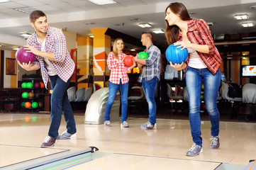 Young friends playing in bowling alley